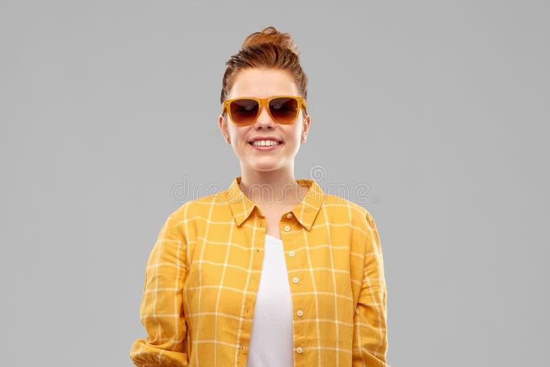 Adolescente pelirrojo sonriente en gafas de sol fotos de archivo