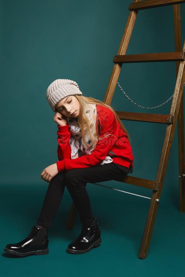 Adolescente pensativo, menina modelo nova bonita com cabelo louro longo em calças de brim pretas e na camiseta vermelha elegante fotografia de stock royalty free