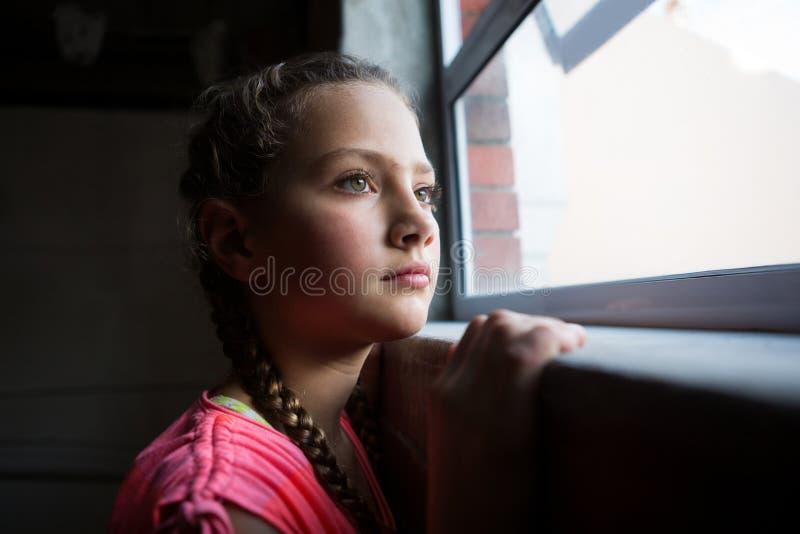 Adolescente pensativo que mira a través de ventana fotos de archivo