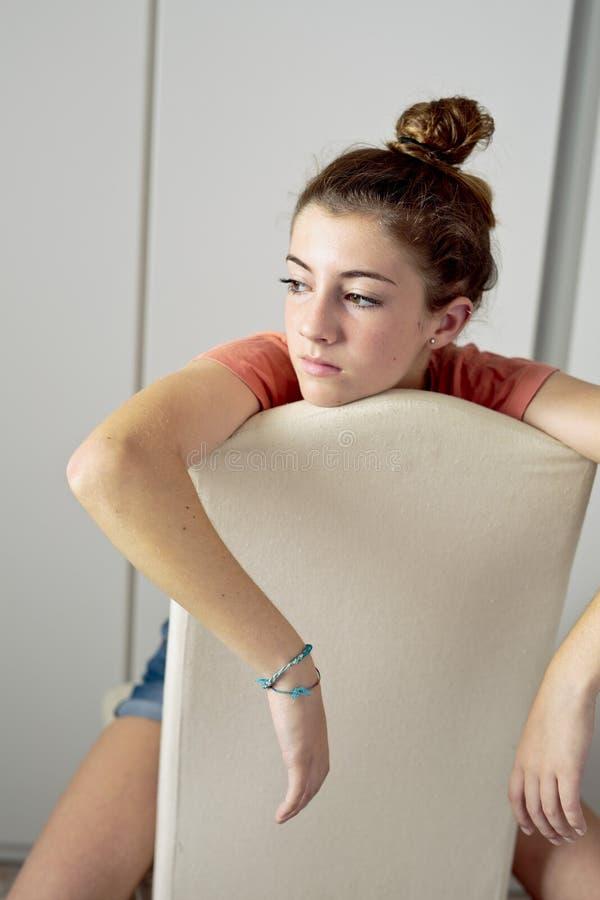 Adolescente pensativo, sentando-se em uma cadeira de cabeça para baixo fotos de stock royalty free