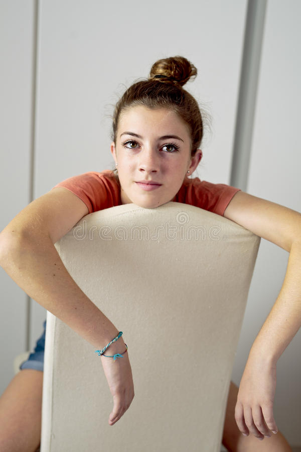 Adolescente pensativo, sentando-se em uma cadeira de cabeça para baixo imagens de stock royalty free