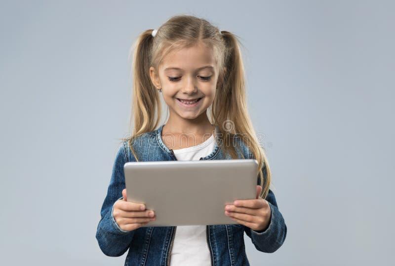 Adolescente pequeno que usa o tablet pc, criança de sorriso feliz da criança pequena imagem de stock