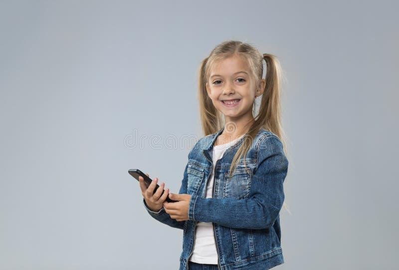 Adolescente pequeno que usa o telefone esperto da pilha, criança de sorriso feliz da criança pequena imagem de stock