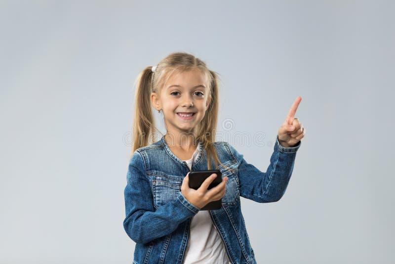 Adolescente pequeno que usa o telefone esperto da pilha, inventor de sorriso feliz pequeno do ponto da criança para copiar o espa imagens de stock