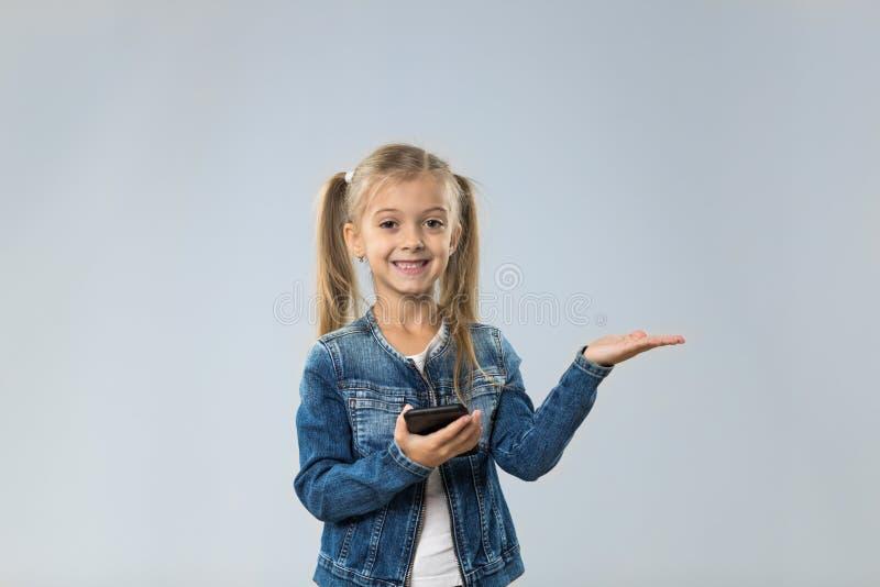 Adolescente pequeno que usa o telefone esperto da pilha, palma aberta de sorriso feliz pequena da criança ao espaço da cópia imagens de stock