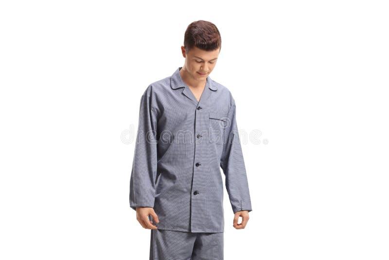 Adolescente in pigiami che guardano giù immagine stock