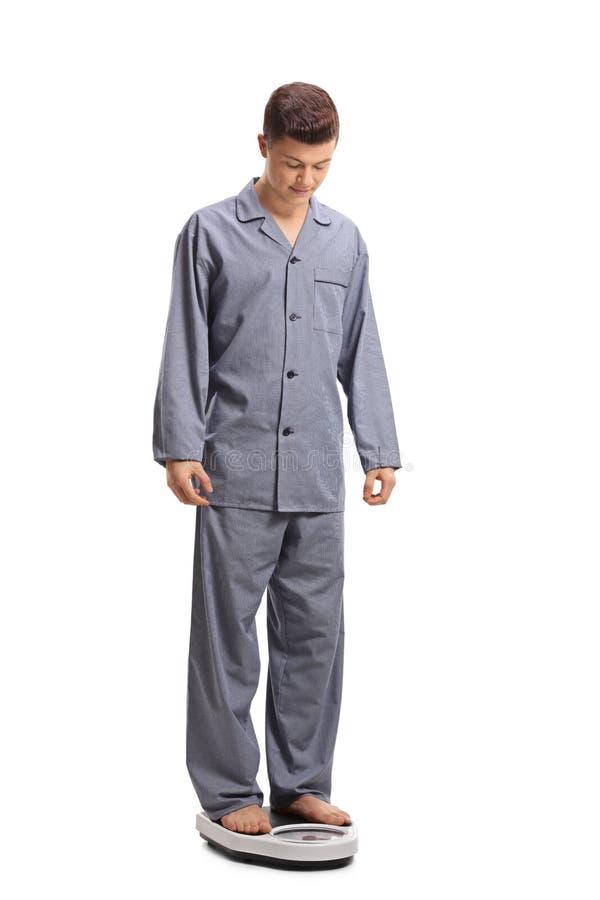 Adolescente in pigiami che stanno su una bilancia immagini stock libere da diritti