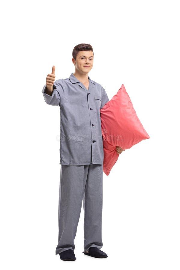 Adolescente in pigiami che tengono un cuscino e che fanno un pollice sul GE fotografia stock libera da diritti