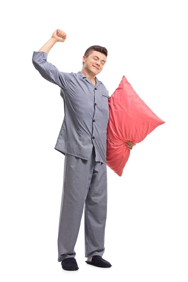 Adolescente in pigiami che tengono un cuscino e che si allungano immagini stock libere da diritti
