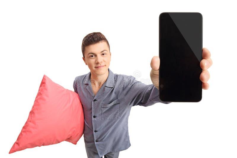 Adolescente in pigiami che tengono un cuscino e un telefono fotografie stock
