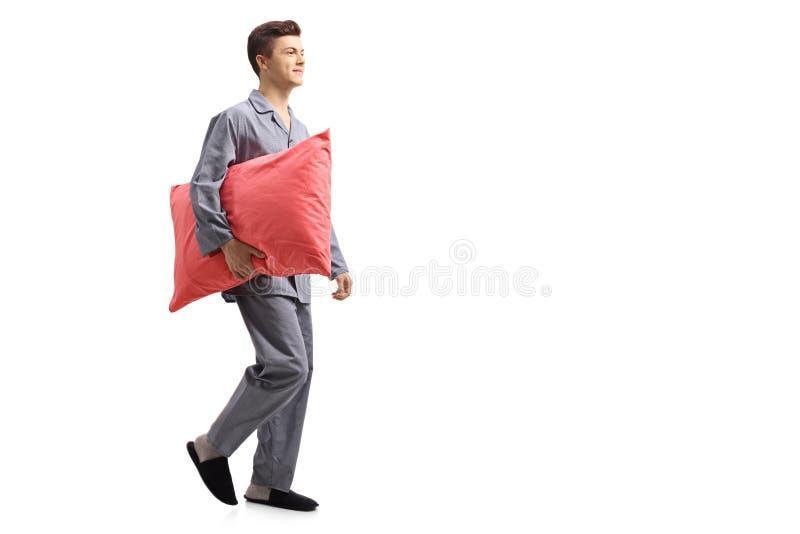 Adolescente in pigiami che tengono un cuscino e una camminata fotografie stock libere da diritti
