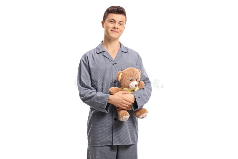 Adolescente in pigiami che tengono un orsacchiotto immagine stock libera da diritti