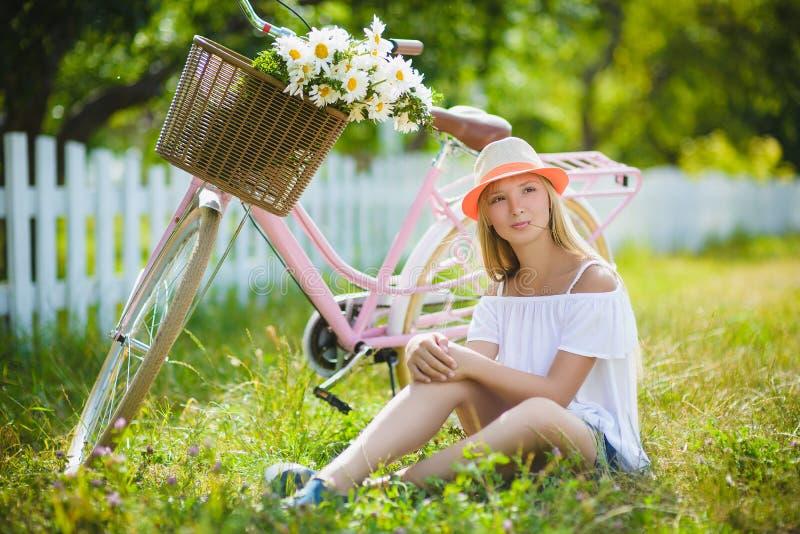 Adolescente posant avec la bicyclette sur le fond du jardin photos stock