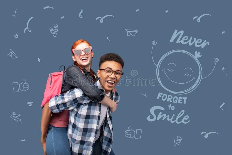 Adolescente positivo que sorri e que retém uma amiga no seu fotos de stock