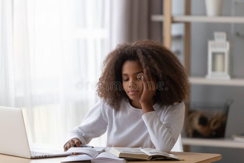 Adolescente preto sonhador confundido de preparar trabalhos de casa fotografia de stock royalty free