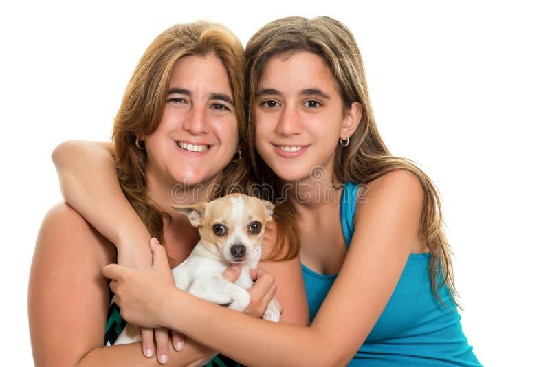 Adolescente que abraça sua mãe e seu cão pequeno fotos de stock royalty free