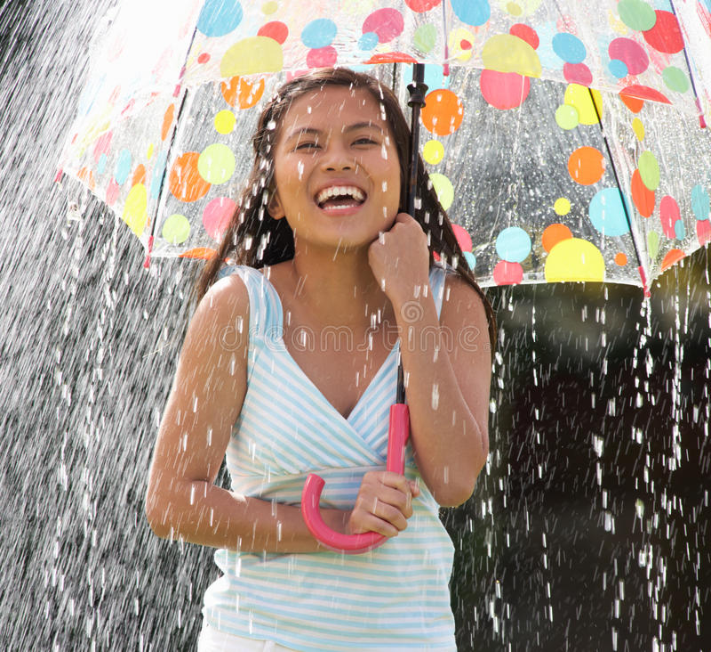 Adolescente que abriga de la lluvia debajo del paraguas fotos de archivo