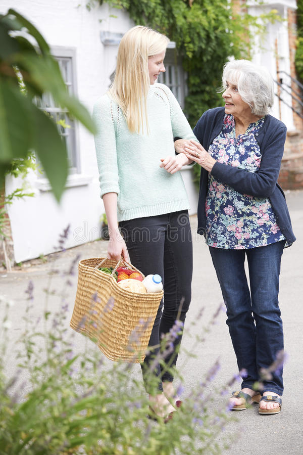 Adolescente que ajuda a mulher superior a Carry Shopping foto de stock royalty free