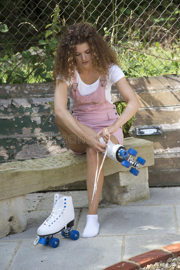 Adolescente que amarra laços em um par de patins de rolo imagens de stock royalty free