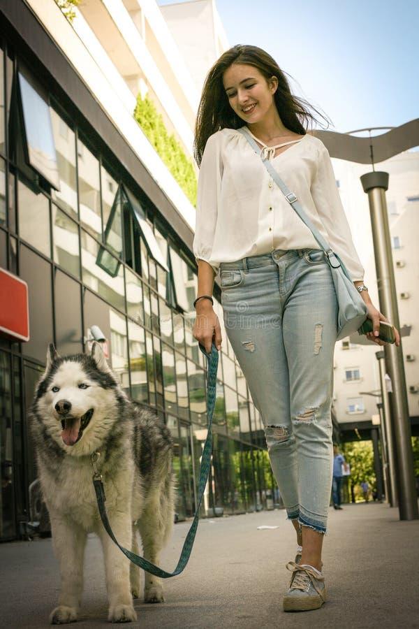 Adolescente que anda com seu cão através da cidade foto de stock royalty free