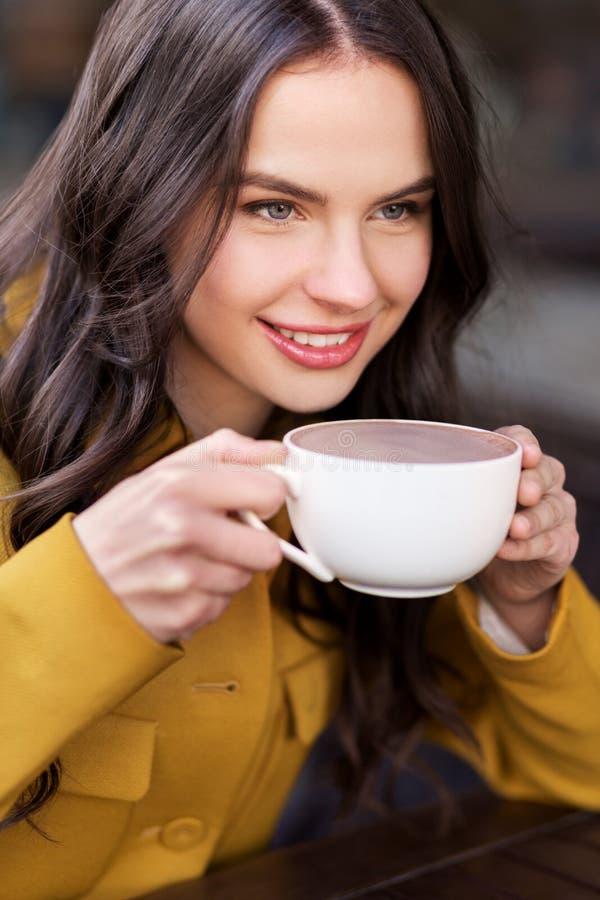 Adolescente que bebe o chocolate quente no café da cidade imagens de stock