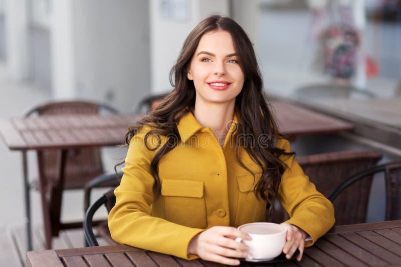 Adolescente que bebe o chocolate quente no café da cidade fotos de stock royalty free