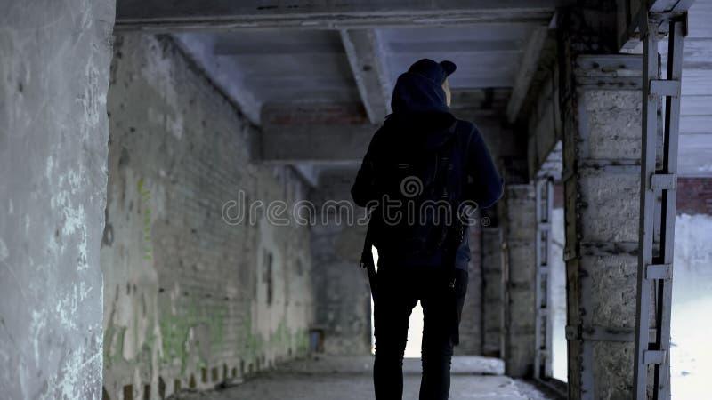 Adolescente que camina en la casa abandonada, lugar peligroso, riesgo de secuestro fotos de archivo