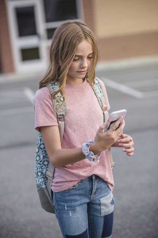 Adolescente que camina a la escuela y que usa su teléfono celular imagenes de archivo