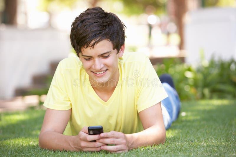 Adolescente que coloca no parque usando o telefone móvel foto de stock