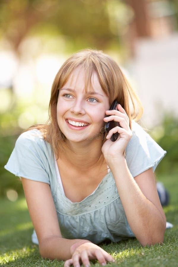 Adolescente que coloca no parque usando o telefone móvel imagem de stock