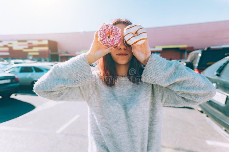 Adolescente que come el buñuelo en la calle de la ciudad afuera fotografía de archivo libre de regalías