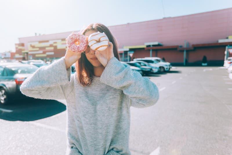 Adolescente que come a filhós na rua da cidade fora imagens de stock royalty free