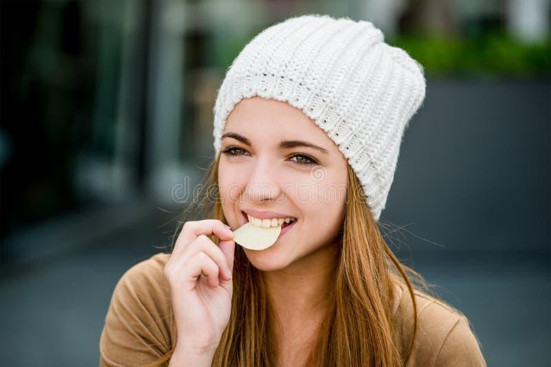 Adolescente que come microplaquetas fotografia de stock royalty free