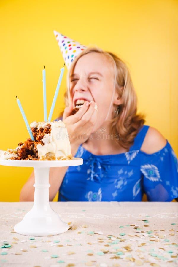 Adolescente que come o bolo de aniversário com suas mãos Um pa da pessoa fotos de stock royalty free