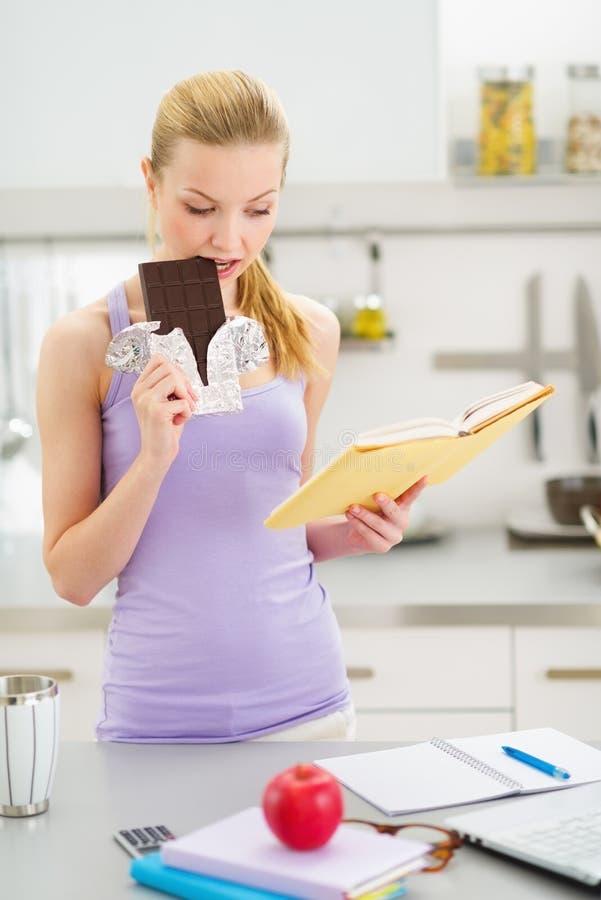 Adolescente que come o chocolate ao estudar imagem de stock royalty free