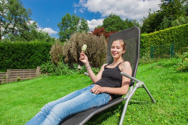 Adolescente que come picolés em um deckchair fotografia de stock royalty free