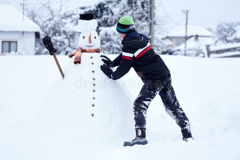 Adolescente que constrói um boneco de neve fotografia de stock