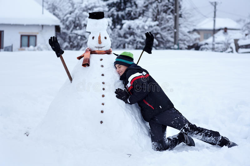 Adolescente que constrói um boneco de neve fotos de stock