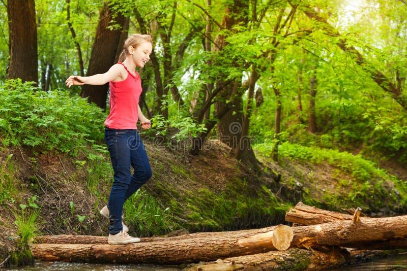 Adolescente que cruza um rio para alcançar o outro lado fotografia de stock