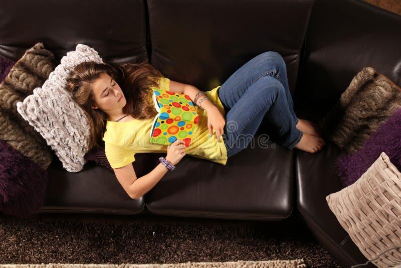 Adolescente que descansa no sofá imagem de stock