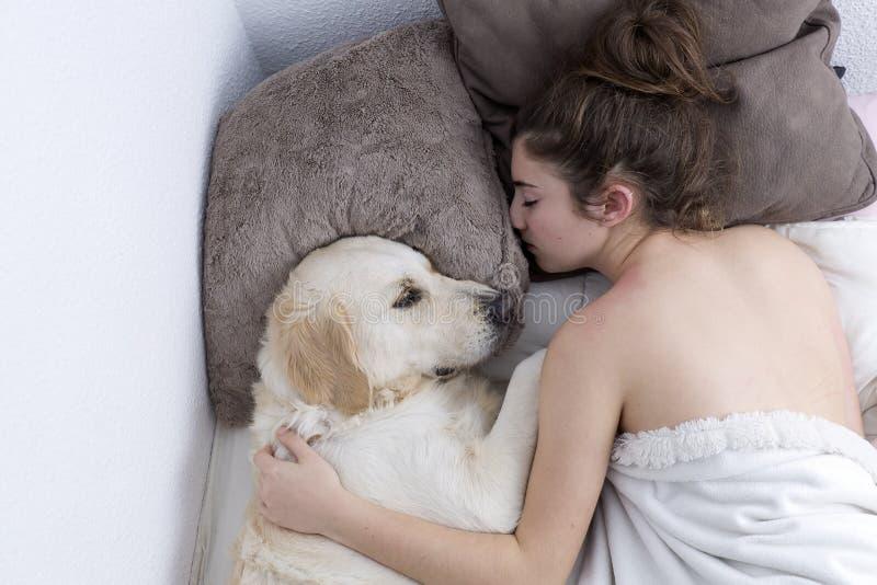 Adolescente que dorme com seu cão imagem de stock