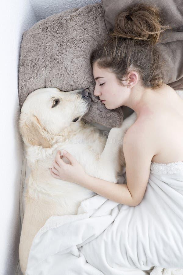 Adolescente que dorme com seu cão imagens de stock royalty free