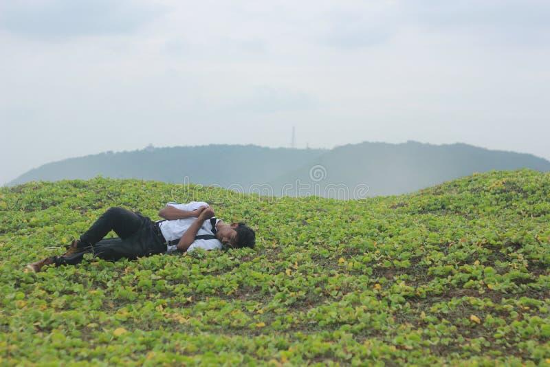 Adolescente que dorme na grama fotografia de stock royalty free