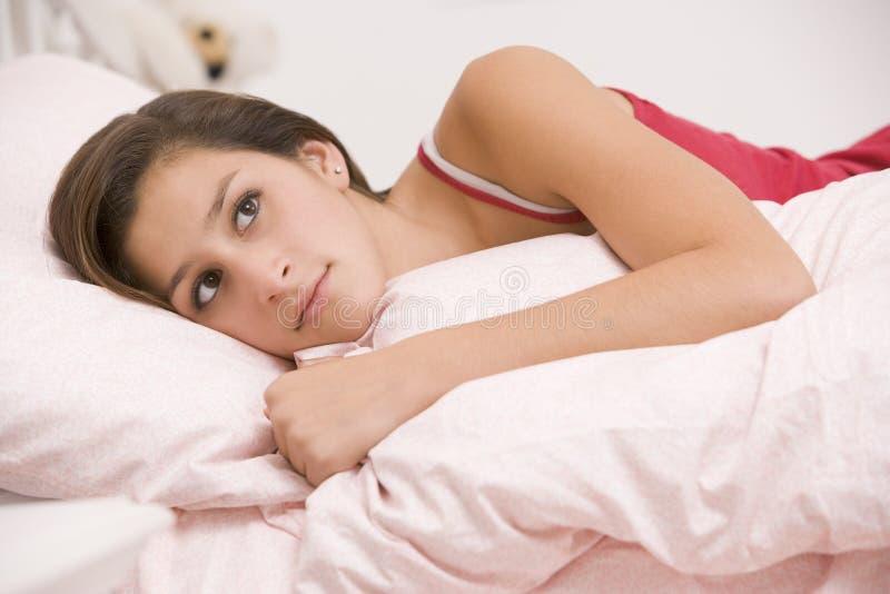 Adolescente que encontra-se em sua cama que olha doente foto de stock
