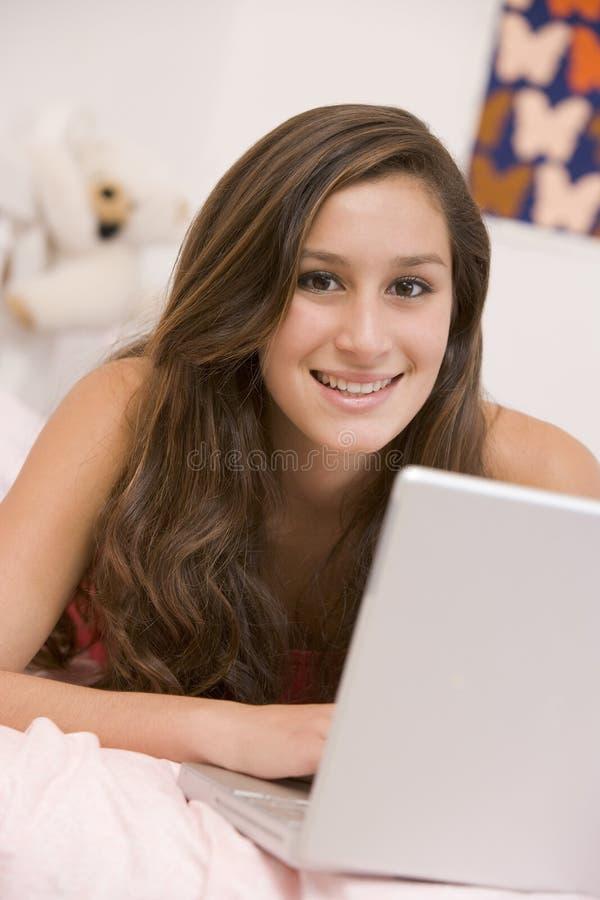 Adolescente que encontra-se em sua cama usando o portátil imagem de stock