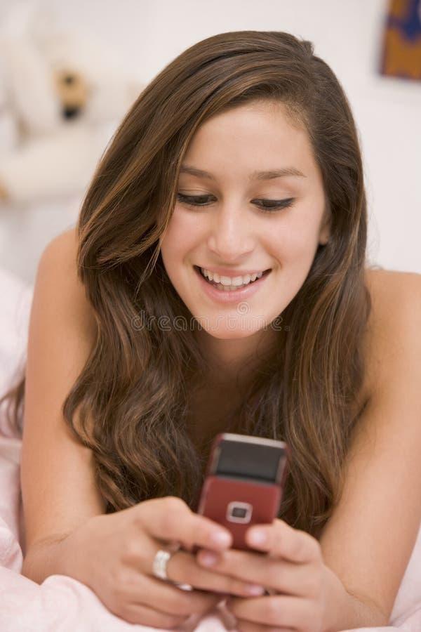 Adolescente que encontra-se em sua cama usando o telefone móvel fotografia de stock royalty free
