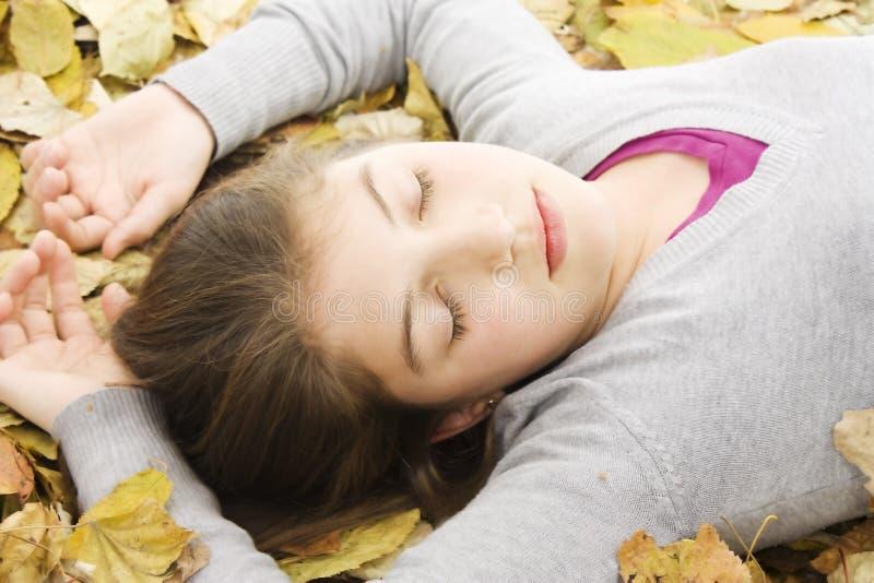 Adolescente que encontra-se para baixo com folhas ao redor. foto de stock royalty free