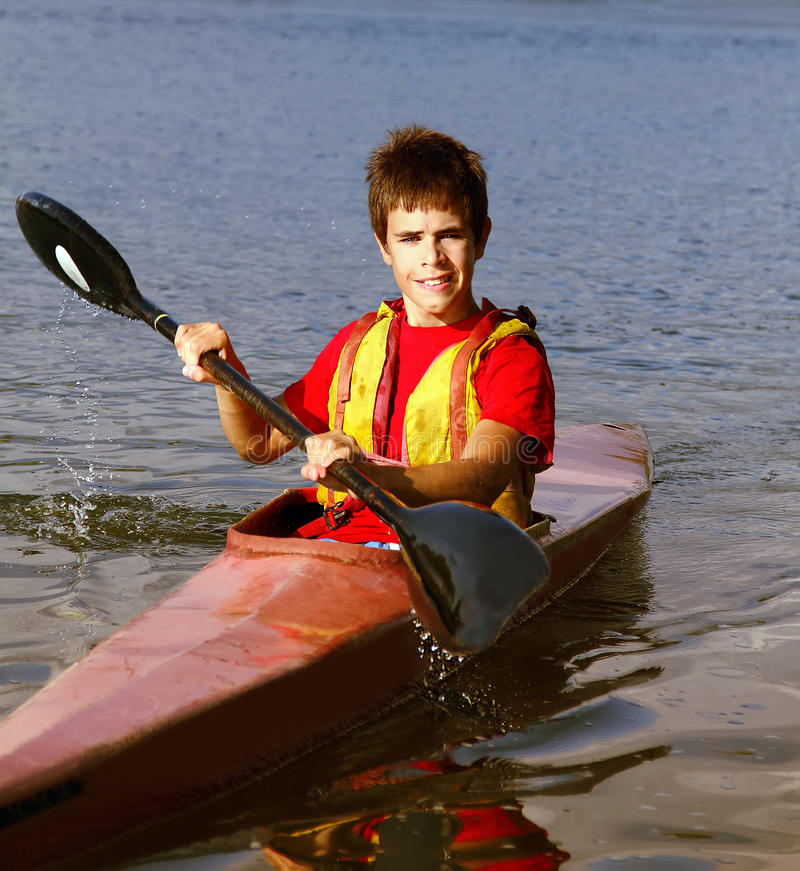 Adolescente que enfileira um barco imagem de stock royalty free