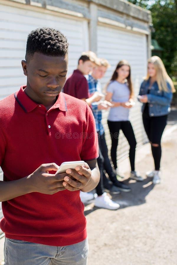 Adolescente que es tiranizado por el mensaje de texto fotografía de archivo