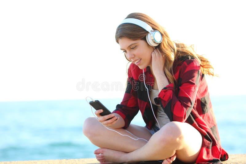 Adolescente que escuta a música que senta-se na praia fotos de stock royalty free